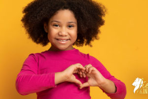 Girl showing unconditional love for herself with hands over heart