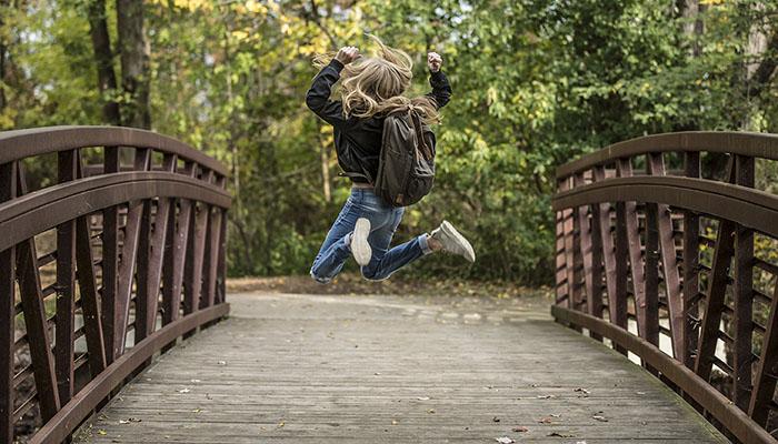 Energised-girl-jumping-on-bridge