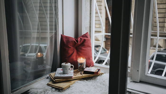 Solitude shown by pillow candle book by window